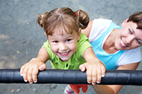 10430531 - portrait of a funny little girl hangs by horizontal bar with mother